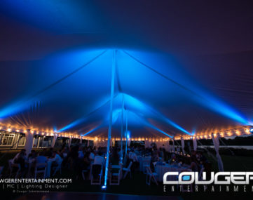 colorfully lit tent over crowded wedding reception