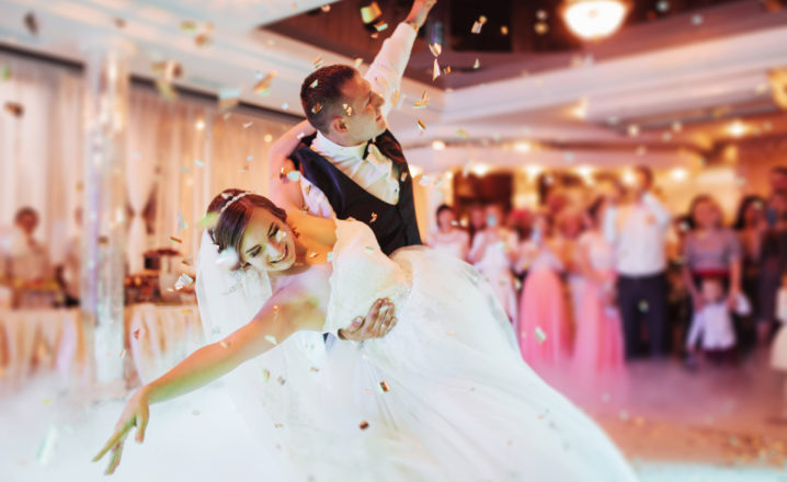bride and groom having first dance with smoke and confetti