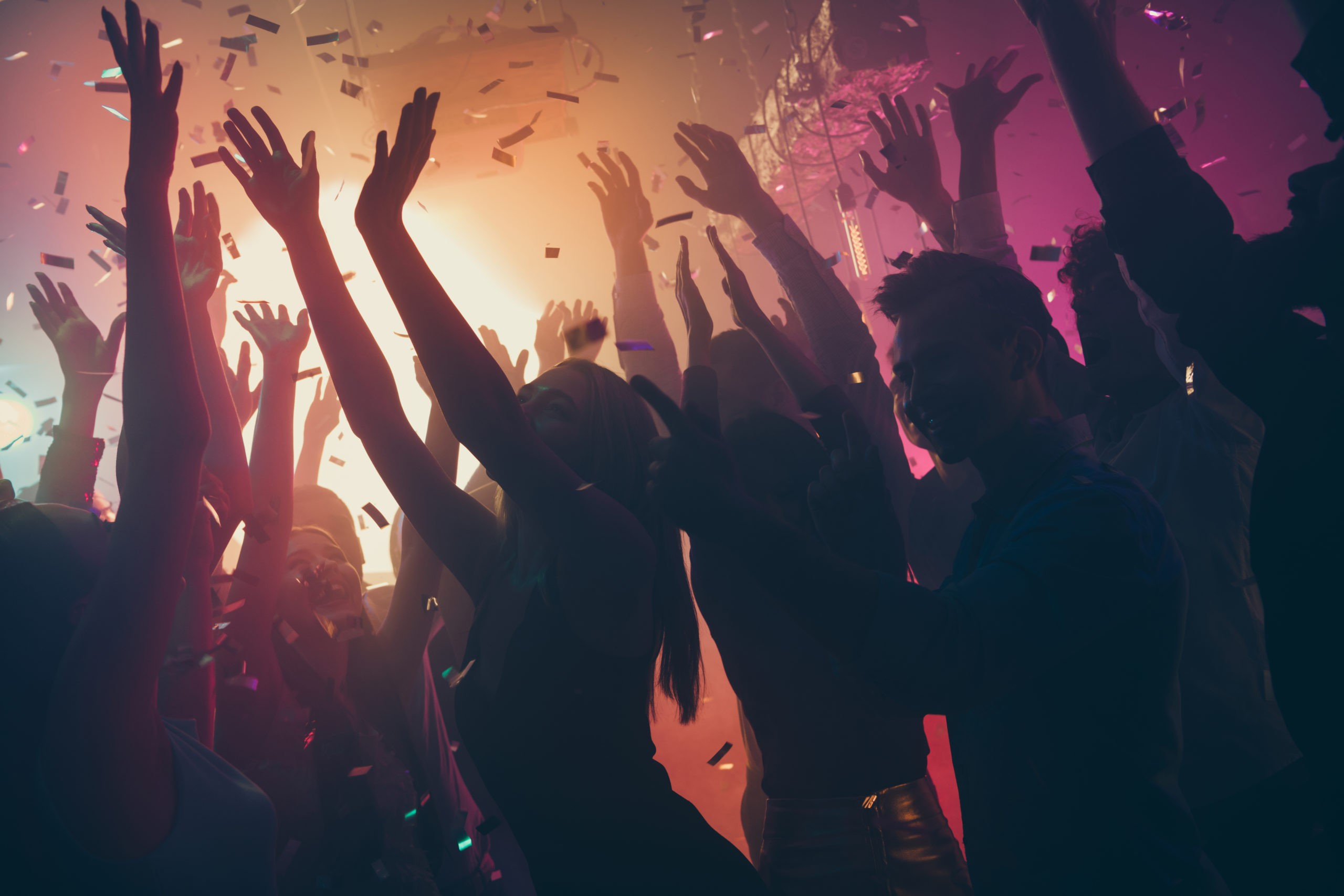 silhouetted young men and women dancing on dance floor with confetti