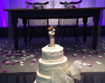 spotlight on wedding cake and table in front of wedding couple table on back lit stage