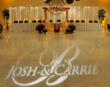 wedding couple monogram projected on dance floor in front of bridal table