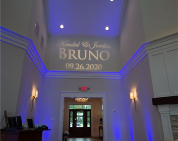 wedding couple name and date projected on wall above reception entrance doorway