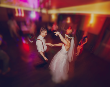 bride and groom dancing excitingly on colorfully lit dance floor