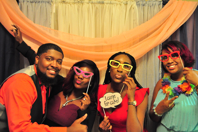 couple and friends posing with comical glasses in booth